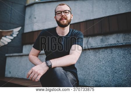 .positive Hipster Guy In Eyewear Sitting Outdoors In Centre Of City