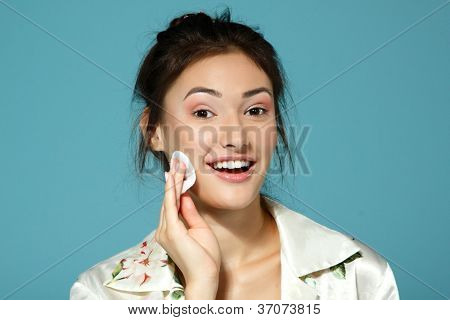 Cheer attractive teen girl clean her face with cotton disk. Morning theme. Over blue background.