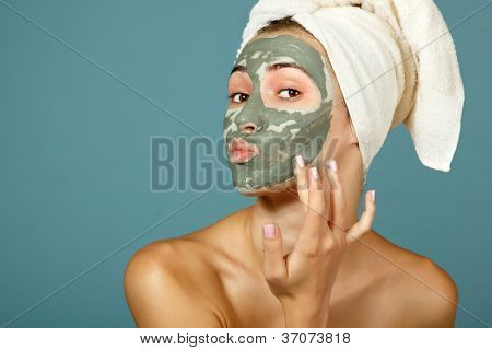 Spa teen girl applying facial clay mask. Beauty treatments. Over blue background.