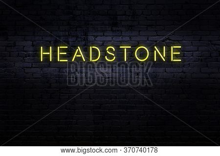 Neon Sign With Inscription Headstone Against Brick Wall. Night View