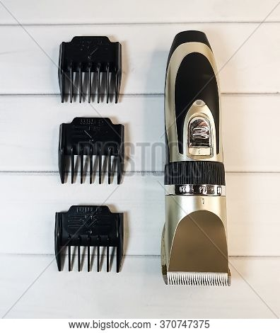 Electric pet clipper, grooming scissors and emery board for pet on a light wooden background. Grooming tools for the hygienic care of pets cats and dogs.