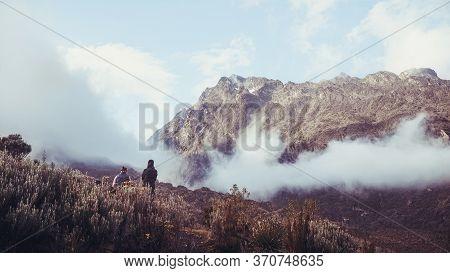 Autumn Season, Mountain Landscape In The Morning, Two Trekkers Watching Sunrise In Rwenzori Mountain