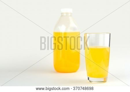A Glass Of Orange Juice Copy Space. Orange Drink In A Plastic Bottle. Orange Juice On A Light Gray B