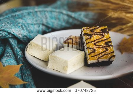 Marshmallows And Orange Dessert On A White Plate. Autumn Dessert. Blue Knitted Scarf. Dry Autumn Lea