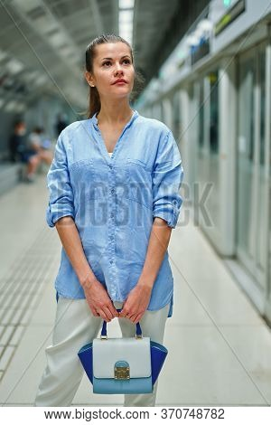 Young Woman With A Handbag In Metro Station Waiting For The Arrival Of Train