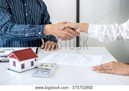 Real Estate Agent And Customers Shaking Hands Together Celebrating Finished Contract After Signing A