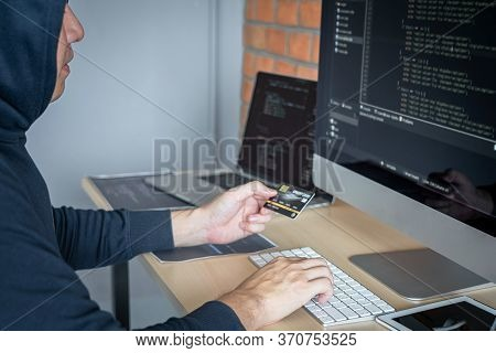Computer Hacker Or Cyber Attack Concept, Dangerous Hooded Hacker Using Multiple Computers Typing Bad