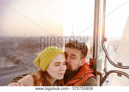 A Couple Man And Woman Ride The Ferris Wheel, Walking In Spring Paris. A Romantic Trip Together. Tou