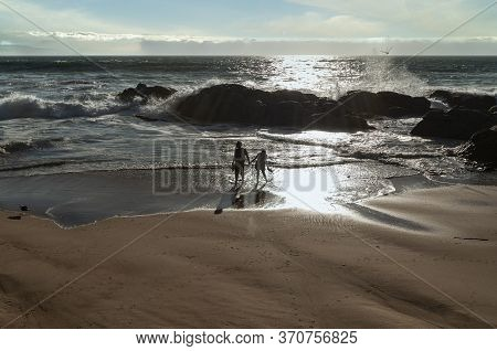 A Young Couple Strolls On The Rocky Beach With The Stormy Pacific Ocean. Central Coast Of Chile