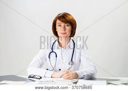 Beautiful Redhead Doctor Writing On Paper In Office. Physician In White Coat With Stethoscope Sittin