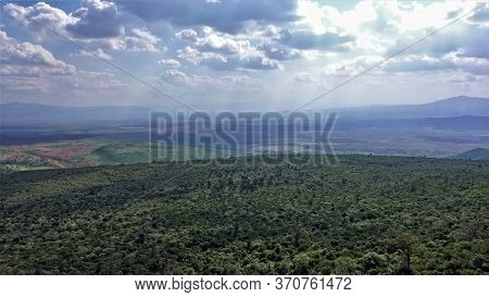 The Great Rift Valley In Kenya Is Lit By The Rays Of The Sun. A Large Area Is Covered With Dense Imp