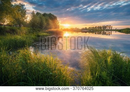 Beautiful River Coast At Sunset In Summer. Colorful Landscape With Lake, Green Trees And Grass, Blue
