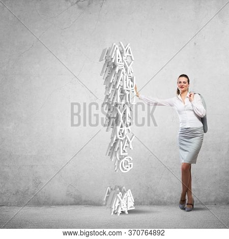 Attractive Businesswoman In Concrete Room Leaning On Exclamation Mark