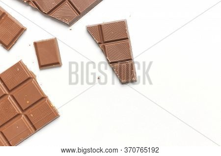 Bar And Pieces Of Milk Chocolate With Nuts Inside On White Background Flat Lay Top View Copy Space.