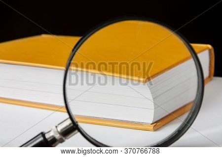 Closed Yellow Book With A Magnifying Glass. Focusing On The Corner Of The Book. Closeup, Selective F