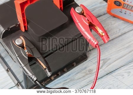 A Car Battery With Red And Black Battery Jumper Clamps And Car Battery Charger On The Background. Cl