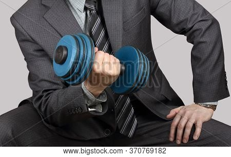 Businessman In A Suit Is Training With Dumbbell. Concept: Business Training. Effort Is Required To A
