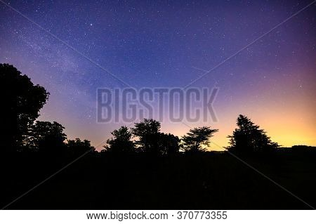 Colourful Long Exposure Star Filled Nightscape With Shooting Stars And Silhouette Trees In The Foreg