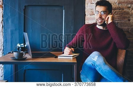 Pondering Bearded Male In Spectacles Talking On Telephone During Sitting Indoors