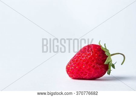 One Strawberry On A White Background. Strawberries In The Lower Right. Place For An Inscription. Cre