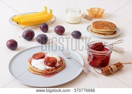 White Wooden Table With Closeup Image Of Dessert Saucer With Crumpets, Pancakes, Sour Cream And Fres