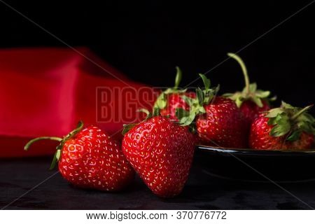 Strawberries On A Black Background. Two Strawberries In The Foreground. Behind A Plate With Strawber