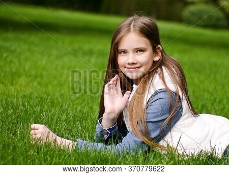 Portrait Of Adorable Smiling Little Girl Child Preteen Lying On Grass In The Park Outdoors