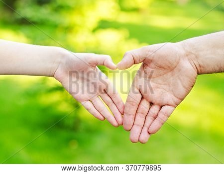 Hands On Heart-shaped Bokeh Background Blurred Outdoor. Family Concept Child And Father Holding Hand