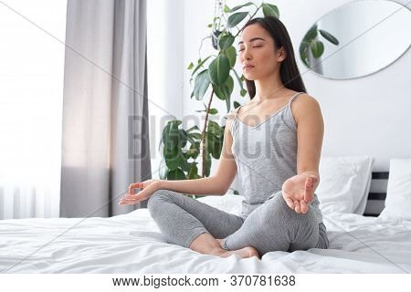 Calm Young Woman Doing Mental Practice On Bed