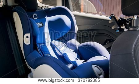 Empty Blue Baby Car Safety Seat On Car Back Seat At Bright Sunny Day