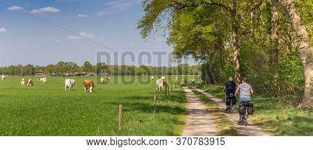 Panorama Of A Couple Riding Their Bicycle At A Dirt Road In Overijssel, Netherlands