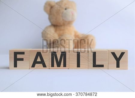 wooden cubes with the inscription family, with a little bear in the background, the concept of family well-being, childhood, education