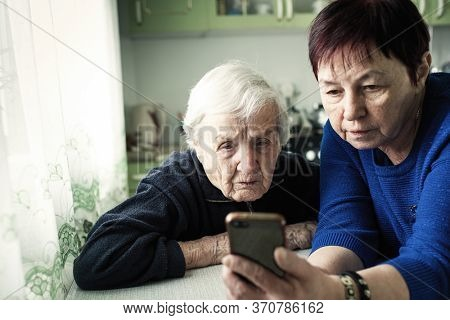 An adult woman shows her old mother a smartphone screen.