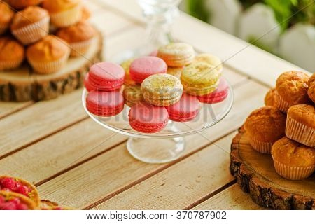 Closeup shot of colorful candy bar with french sweets macarons lying on glass plate. Macarons a placed in a middle of a frame with tasty cupcakes accompanied on both sides of horizontal picture
