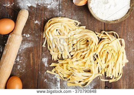 Homemade Pasta On A Wooden Table Background, Eggs, Flour, Rolling Pin. Family Cooking Concept. The C