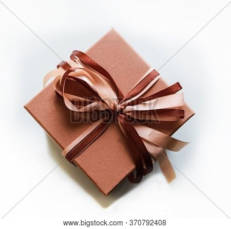 Beige Squared Present Box With Beige And Brown Ribbon On Beige Background