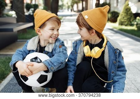 Two Cute Twin Boys Sitting On The Skateboard Or Pennyboard Looking Each Over Up In The Street.