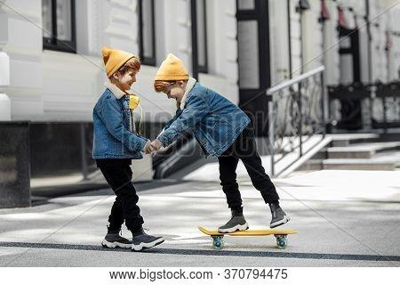 Two Joyful Twin Boys Play With Skateboard Or Pennyboard In The Street.