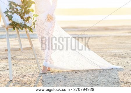 Young Woman In White Dress On The Beach. It Stands Next To An Easel Decorated With Flowers. On The S