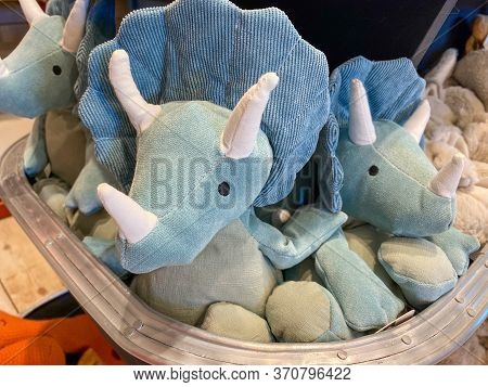 A Bin Of Blue Stuffed Triceratops Dinosaur Toys At A Retail Store.