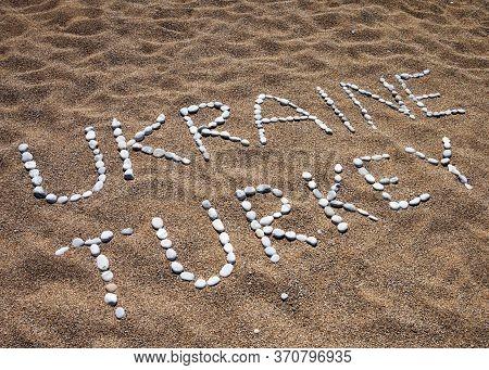 Words Ukraine, Turkey And Smile Composed Of Pebble Stones On Sand Beach At Summer