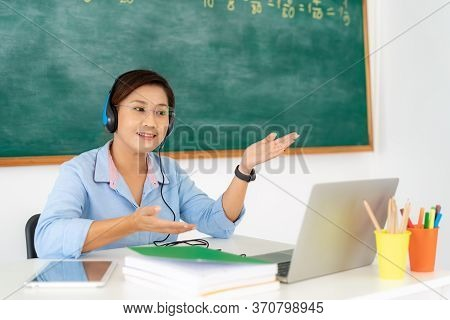 Asian Woman Teacher Teaching And Explain With Student Via Video Conference E-learning In Laptop At C