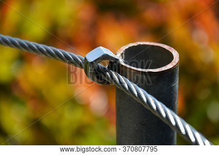 A Close Up Image Of A Wire Boundary Rope Welded To A Metal Pole To Create A Safety Boundary In A Woo