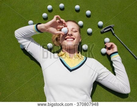 Young female golfer lying on green holding ball in front of eye view from above