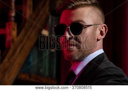 A close-up portrait of a brutal handsome businessman in sunglasses. Men's beauty, fashion. Optics for men.