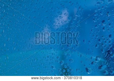 Raindrops On The Surface Of Window Panes Natural Pattern Of Raindrops, On A Blue Background.