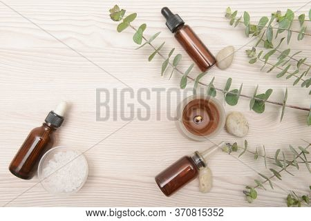 Eucalyptus leaves and candle , bottles of essential oil ,stones,salt in bowl,on wooden background