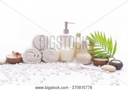 Spa setting with Green palm , bottles of essential oil l , herbal ball, salt in bowl ,candle , herbal ,ball ,spoon on pile of white stones