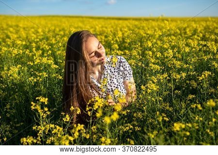 A Girl In A Canola Field, With Her Hair Loose, Sniffs Canola.