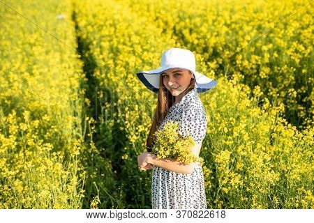 Girl In With A Bouquet Of Rapeseed, In A Rapeseed Field. In A Hat And Dress.